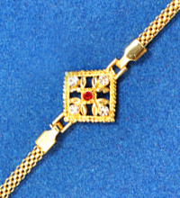 Golden Rakhi Bracelet with White And Red Stones