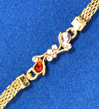 Golden Rakhi Bracelet with Red and White Stones